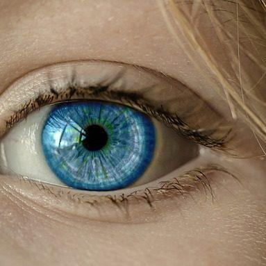 Das Auge und die Blue Iris einer blonden Frau
