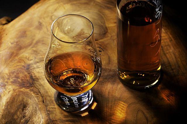 Ein Holzstamm auf dem eine Schnaps Flasche und ein Glas stehen